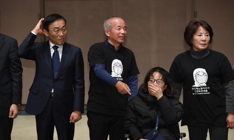 Le vice-président de Samsung Kim Ki-nam, à gauche, (L) pose avec Hwang Sang-ki, à l'origine du mouvement contre la firme après la mort de sa fille d'une leucémie.  Ph. AFP